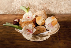 Basket with bread. Basket with buns and flowers on a wooden table Stock Photo