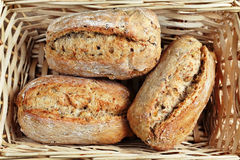Basket and bread. Close up of whole grain rolls placed in wooden bread basket Stock Images