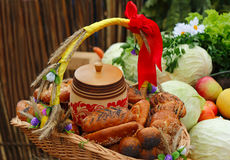 Basket of bread, decorated with ribbons, and vegetables Royalty Free Stock Photos