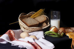 сbasket with bread, egg, onion and milk Royalty Free Stock Photos