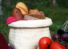 A basket with bread at a picnic. A basket with different kinds of bread at a picnic table, blur background Stock Photography