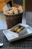 Basket of bread and plate of olives on table Royalty Free Stock Images