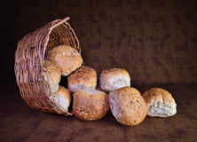 Basket of bread rolls. A tipped over basket with bread rolls stock photo