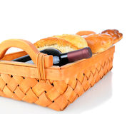 Basket with Bread and Wine. A basket with loaves of bread and a wine bottle over a white background with slight reflection Stock Image