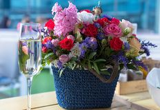 Basket with bright flowers and a glass of champagne at table Royalty Free Stock Photos
