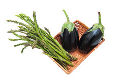 Basket with bunch of asparagus and aubergines isolated Royalty Free Stock Photo