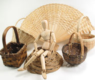 Basket Case. An artist's mannequin sits amid woven wood baskets Stock Image