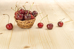 Basket of cherries. On natural wood Royalty Free Stock Image