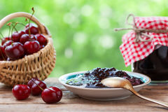 Basket with cherry and  jar of jam. Stock Photography