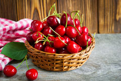 A basket with cherrys on wooden table stock photography