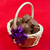 Chocolates in basket. A closeup of a wicker basket of milk chocolates Stock Image