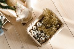 Basket with Christmas balls and toys under the Christmas tree. Preparing to decorate the Christmas tree. Silver and golden balls,