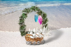 Basket with Christmas decorations on a beach at the region of the sea Stock Images