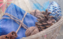 Basket with Christmas presents decorated with linen cord, cinnamon, walnuts, pine cones, Christmas Decorations.Snow drawn. Stock Photography