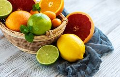 Basket with citrus fresh fruits. On the white wooden table royalty free stock photo
