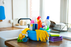 Basket with cleaning items on blurry background white citchen. C Stock Photography