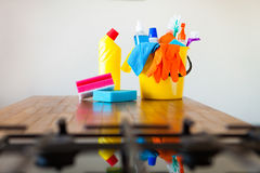 Basket with cleaning items on blurry background white citchen. C Stock Photos