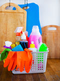 Basket with cleaning items on blurry background white citchen. C Royalty Free Stock Photography