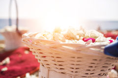 Basket closeup with petals. wedding in cyprus, bride and groom on a stone bridge in Agia Napa. arch and table for Stock Photo