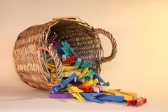 Basket with clothespins. Basket with coloured clothespins in side position stock photography