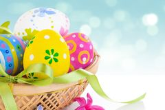 Basket with colored easter eggs in the sky background royalty free stock image