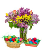 Basket with colored easter eggs and transparent vase Stock Images