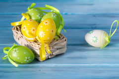 Basket with colored Easter eggs on a wooden background Stock Photography