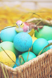 Basket of colored eggs Stock Photos