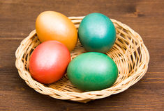 Basket with colored eggs on wood Stock Photography