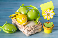 Basket with colored eggs and wooden flower note holder on a wooden background Royalty Free Stock Photo