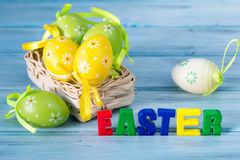 Basket with colored eggs and word easter made of magnet letters Stock Images
