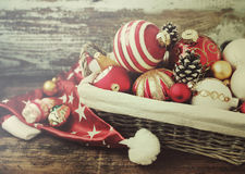 Basket with colored glass toys and balls, cones, Santa`s cap, decoration and gifts on wooden background. Stock Photo
