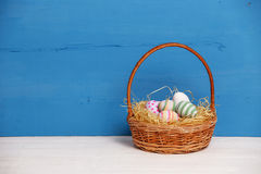 Basket with colorful Easter eggs, close up photo Stock Photo