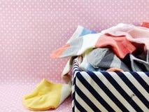 Basket of colorful socks on pink polka dot background Stock Photos