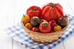 Basket with colorful tomatoes. On a white wooden board Stock Image