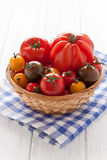 Basket with colorful tomatoes. On a white wooden board Royalty Free Stock Photos