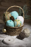 Basket with colorful yarns decoarted with pine brunch Royalty Free Stock Photos