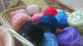 A basket of coloured cotton reels. A wicker wooden basket box full of different brightly coloured colourful balls of cotton string wool reals. A collection group royalty free stock images