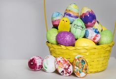 Coloured painted eggs and toy chick are shown in a basket for easter. A basket of coloured eggs and toy chicks are shown ahead of Easter royalty free stock photos