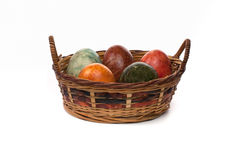 Basket of coloured eggs. Wicker basket of  coloured eggs Stock Images