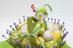 Basket with colourful eggs and a cock Stock Photography