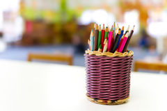 Basket of colourful kids pencils. On table Stock Photography