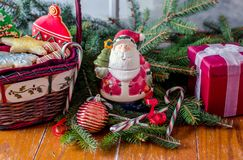Basket of cookies with Santa statue and gift box. A basket of decorated sugar cookies is next to a Santa statue and a silk red gift box, in this festive holiday Royalty Free Stock Image