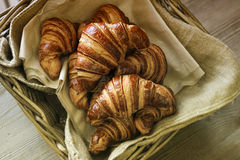Basket with croissants. Fresh croissants in a basket on a wooden background Stock Image