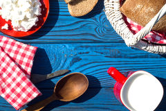 Basket, a cup of milk, cottage cheese and bread on a table of bl Royalty Free Stock Photography