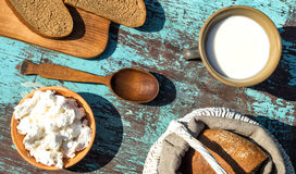 Basket, a cup of milk, cottage cheese and bread on a table of li Stock Photo