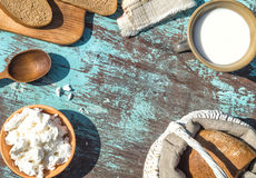 Basket, a cup of milk, cottage cheese and bread on a table of li Stock Photos