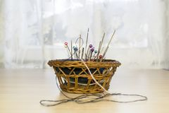 A basket with a cushion for needles. A seamstress-tailor. Needles, pins stock image
