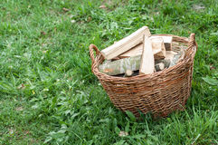 Basket of cut logs fire wood on green grass, environmental conce Stock Photos