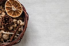 The basket with decorative elements lies on a white warm textural scarf or blanket. In the basket of dried flowers. Orange, citrus, spices. The concept of stock photos